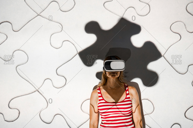 Unrecognizable young female in casual outfit and virtual reality goggles exploring cyberspace with puzzle pieces