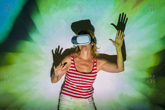 Unrecognizable young female in casual wear and VR headset getting new experience and touching virtual object in room with colorful projector illumination