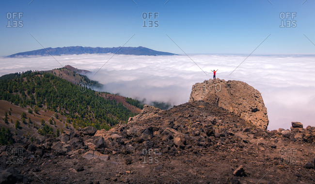 Back view of anonymous male traveler standing on rocky hill in highlands and enjoying amazing view of clouds