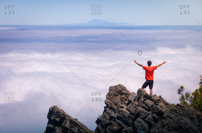 Back view of anonymous male traveler standing with outstretched arms on rocky hill in highlands and enjoying amazing view of clouds