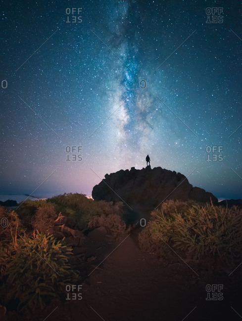 Back view of unrecognizable traveler male standing on hill while admiring spectacular scenery of milky way over mountainous in starry night
