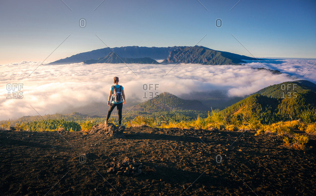 Back view female traveler standing on hill while admiring spectacular scenery on clouds over mountainous terrain