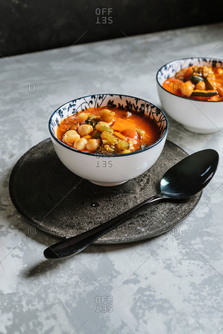 Vegan food, chickpeas stewed with tomatoes, zucchini carrots and peppers on bowl