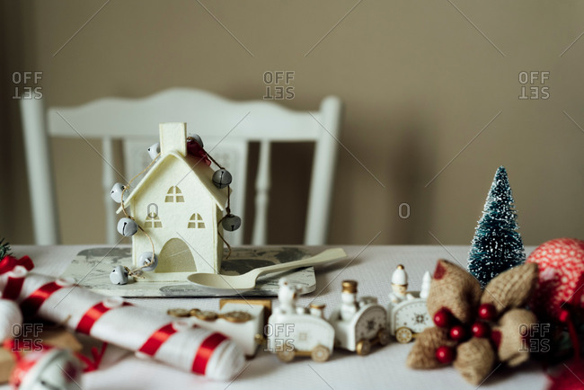 Miniature white house with garland placed on table with various Christmas accessories and spoon