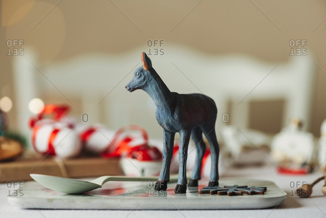 Creative festive table setting with toy animal figurine placed on platter with spoon during home Xmas party