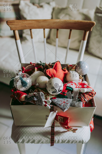 Various colorful decorative craft toys for Christmas celebration in box placed in cozy room during holiday preparation