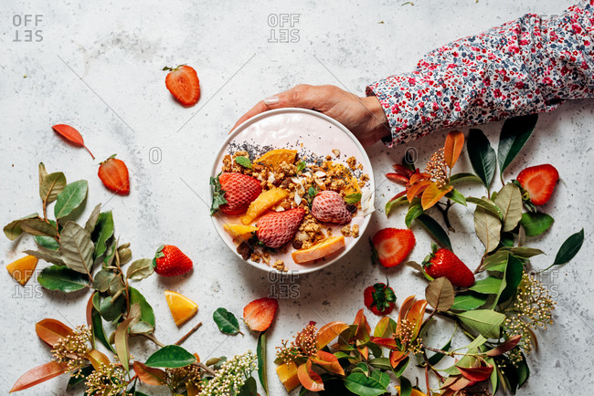 From above of unrecognizable female with smoothie bowl with fruits and berries sitting at table during breakfast in morning