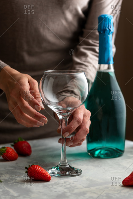 Unrecognizable female standing at table with crystal glass and bottle of alcohol drink while preparing ingredients for strawberry cocktail