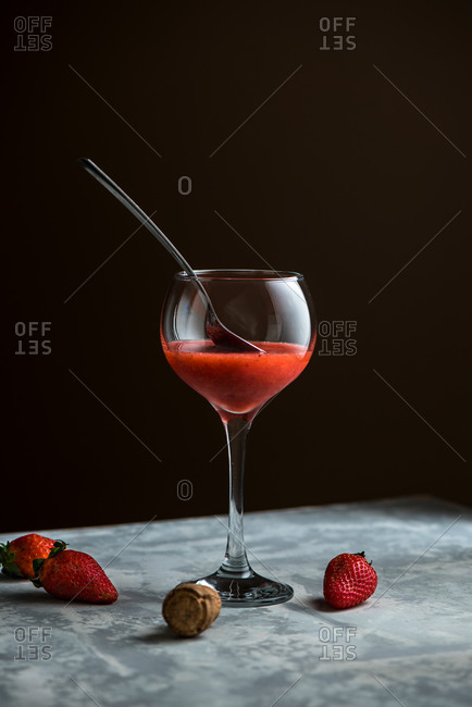Refreshing strawberry alcohol cocktail in glass placed on table with berries in studio on brown background