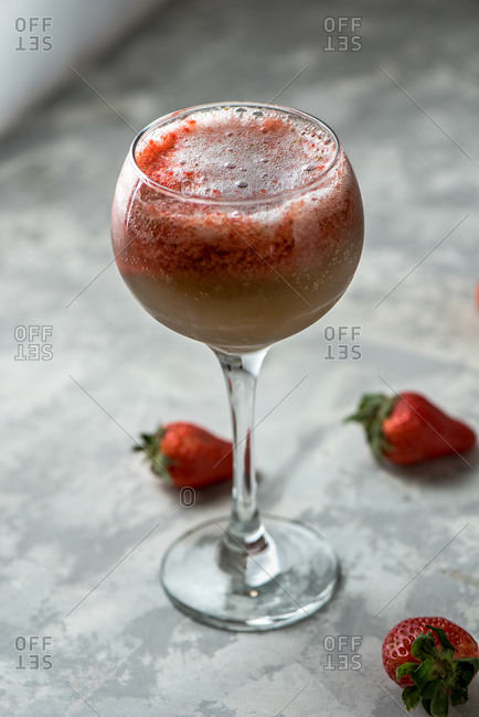 Refreshing strawberry alcohol cocktail in glass placed on table with berries in studio