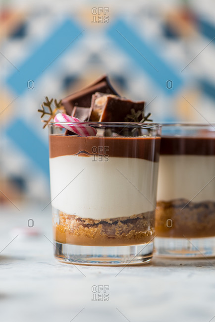 Yummy vanilla and chocolate dessert in glass cup decorated with Christmas items
