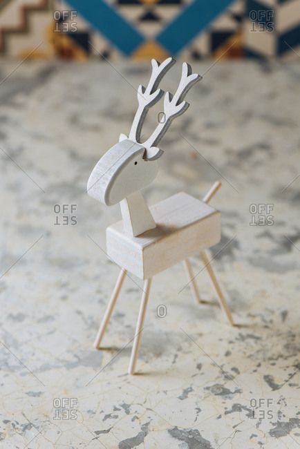 Closeup of handmade miniature wooden deer figurine painted in white color for Christmas decor