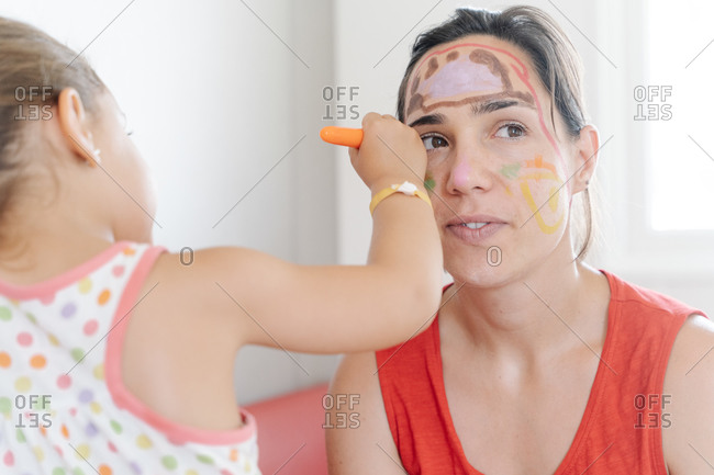 Side view of adorable little kid painting pictures on face of mother while entertaining during weekend at home