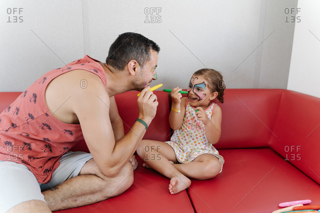 Side view of adorable girl painting face of calm father while relaxing together on sofa and having fun during weekend