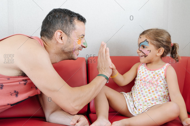 Side view of smiling man and little girl with funny painted faces relaxing on sofa at home while giving high five and looking at each other