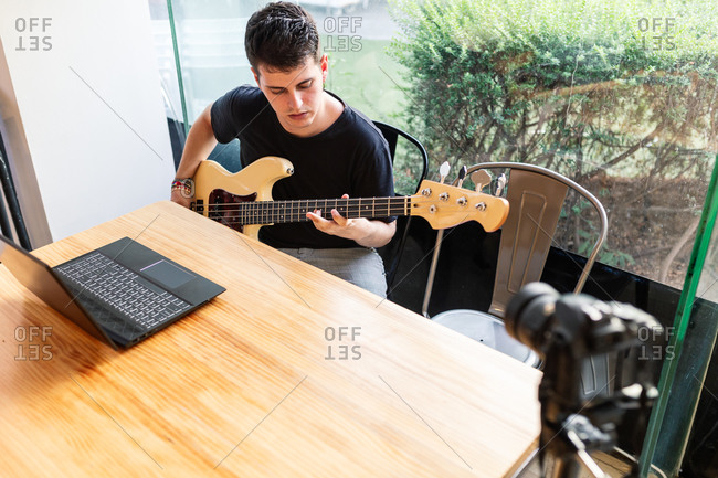 Focused young male musician sitting near window and performing music on bass guitar