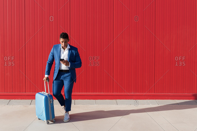 Full body of young African American man in elegant blue suit with luggage messaging on mobile phone while standing against red wall on street
