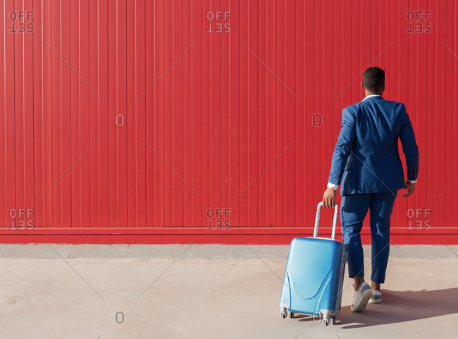 Full body back view of unrecognizable ethnic businessman in elegant formal suit pulling suitcase while walking against red wall