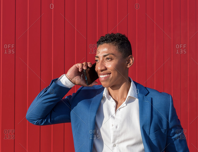 Young well dressed African American male in formal clothes having serious phone conversation while standing against red wall
