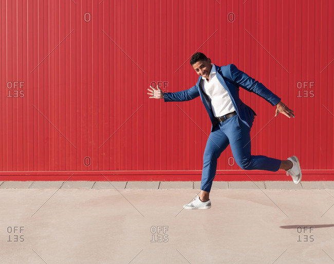 Full body side view of optimistic young African American businessman in stylish suit and sneakers running and jumping against red wall