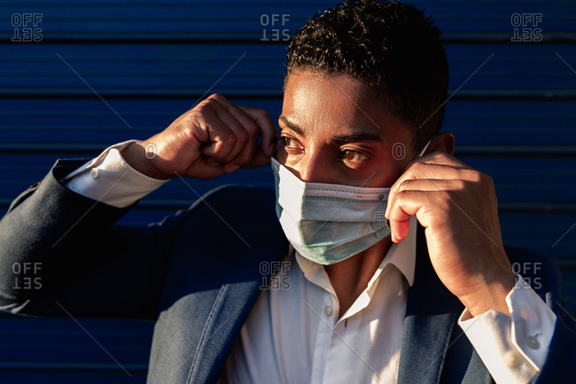 Young African American male in formal outfit putting on medical mask for coronavirus prevention