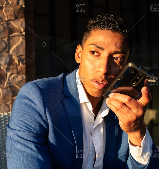 Young successful well dressed black businessman in elegant suit sitting in chair and having pleasant conversation on mobile phone