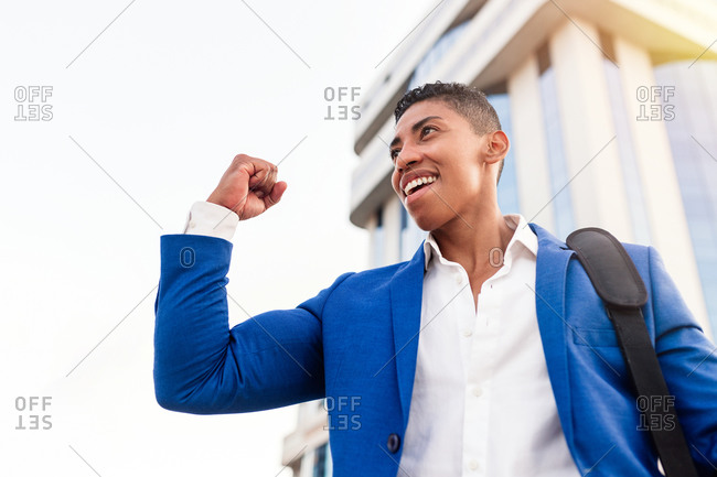Low angle of cheerful young African American male manager in formal blue suit celebrating successful deal while standing against modern city building