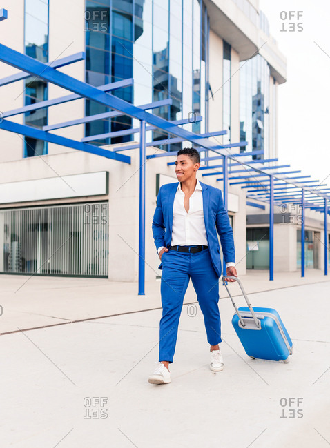 Full length of confident young ethnic male entrepreneur in stylish outfit with suitcase walking near modern building