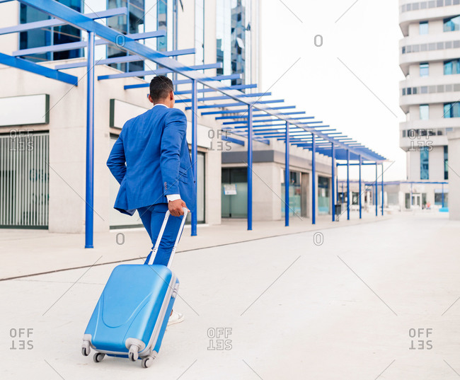 Full body back view of unrecognizable ethnic businessman in elegant formal suit pulling suitcase while walking