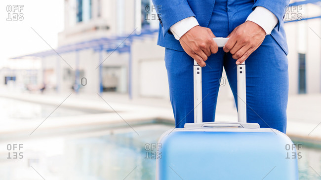 Stylish businessman with suitcase in city