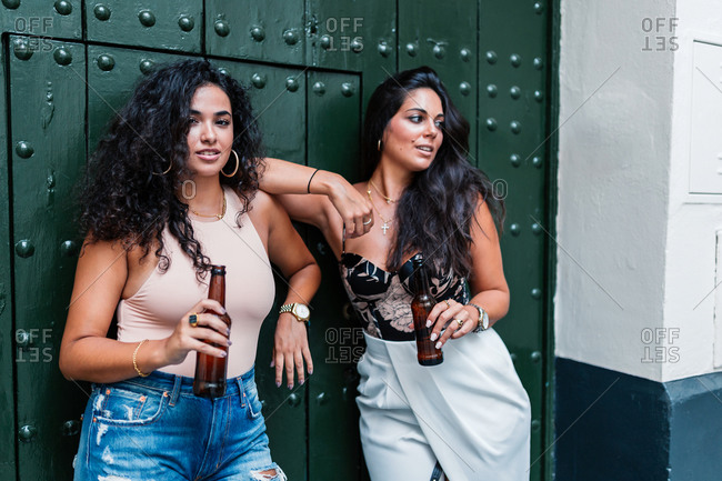 Positive relaxed young Latin girlfriends having a few beers while chilling together against green wall