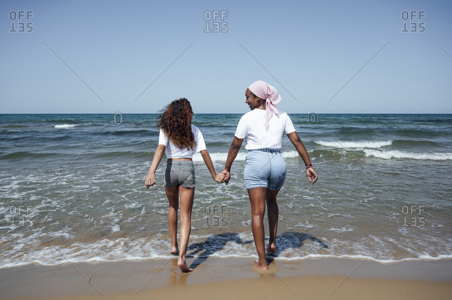 Cheerful black mother and daughter at seaside
