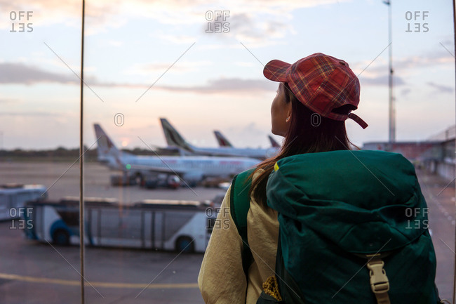 Back view of young Asian female traveler with backpack standing near window in airport terminal and observing airplanes while waiting for flight in Sri Lanka