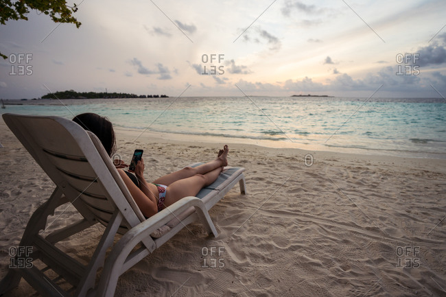 Back view of unrecognizable female tourist in bikini sitting on chair and browsing mobile phone while spending evening on sandy beach during summer holidays on Maldives islands