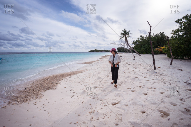 Full body front view of young Asian female traveler walking on tropical beach with white sand and blue sea water while spending summer holidays on Bodufolhudhoo island in Maldives