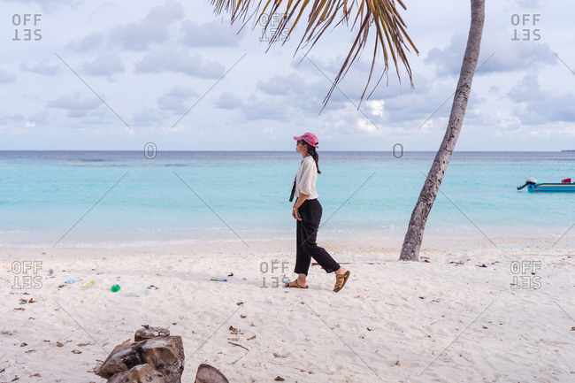 Full body side view of young Asian female traveler walking on tropical beach with white sand and blue sea water while spending summer holidays on Bodufolhudhoo island in Maldives
