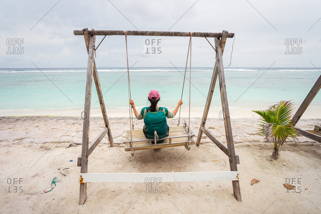 Back view of unrecognizable female traveler sitting on swings and enjoying fresh breeze while resting during summer holidays on sandy beach of Hulumale island in Maldives