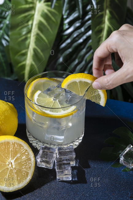 High angle of crop unrecognizable person with slice of lemon near table with glass of refreshing cocktail with ice cubes