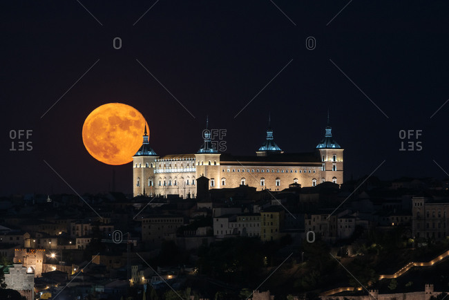 Amazing view of bright full moon in dark night sky over old town with glowing historical palace