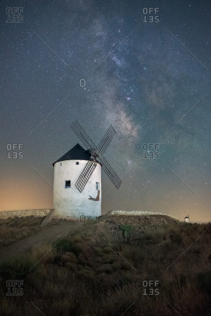 Low angle of old white windmill tower located on hill against starry night sky with Milky Way