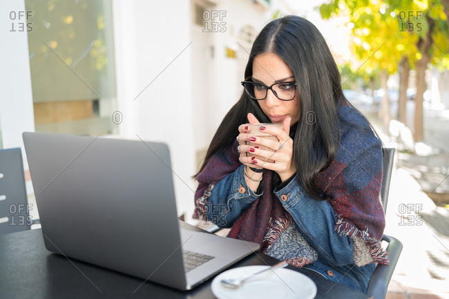 Young brunette woman drinks hot coffee on the terrace of a bar protected by a blanket while she consults her laptop