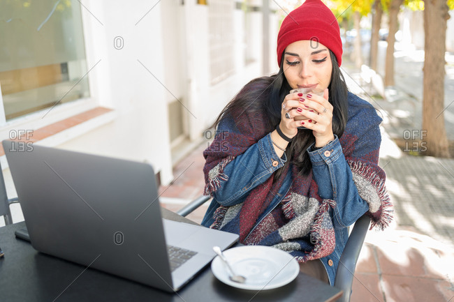 Young brunette woman warms her hands with a hot cup of coffee on the terrace of a bar protected by a blanket while she checks her laptop