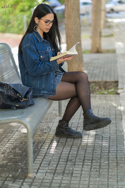 Portrait of a young black-haired woman reading a book sitting on a park bench