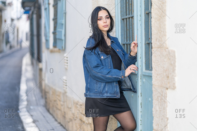 Distracted young woman with long black hair by the door of her house