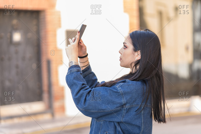 Young woman with long black hair doing a self-portrait in the street
