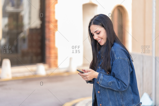 Happy young woman with long black hair consulting her mobile phone in the street