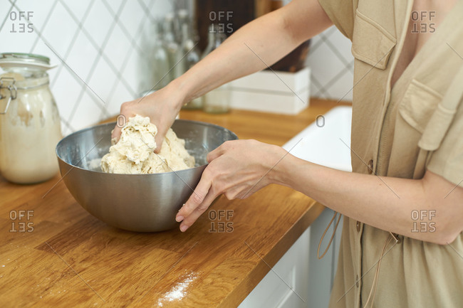 Female hands mixing a dough for homemade bread loaf