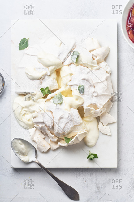 Pavlova meringue cake with fresh mint and wine poached plums