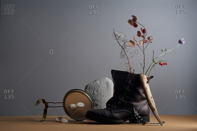 Still life with field plants, feathers, rock and leather shoe