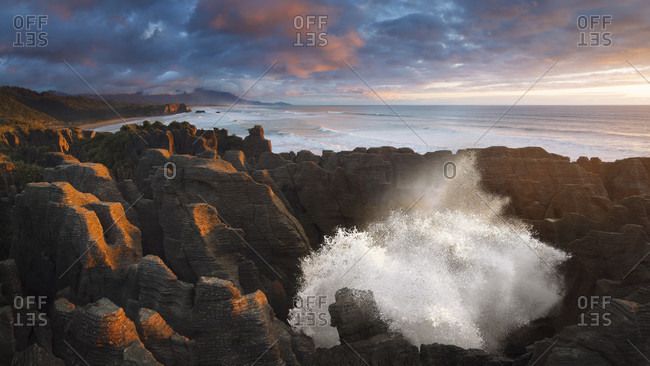 Fountain from a blowhole at Pancake Rocks in the sunset, Punakaiki, Paparoa National Park, New Zealand